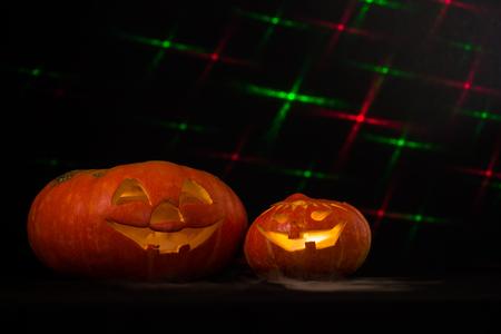 spew: Two halloween pumpkins spew smokeBlack background with laser effects