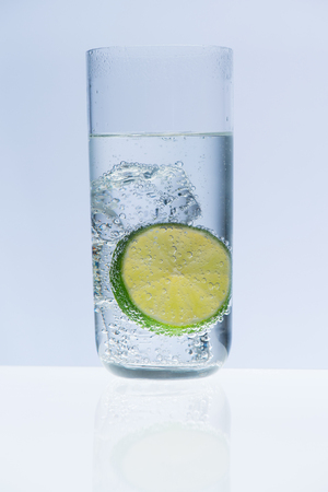 alcohol: Cold glass of water, soda or alcoholic drink whith lime slice on white background
