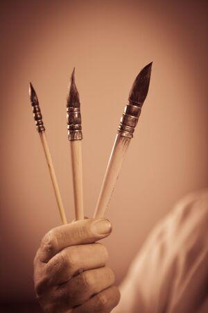 draftsman: Painters hand holding three paintbrushes