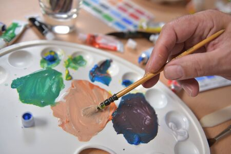 stroking: Artists hand applying paint gouache on the drawing sheet