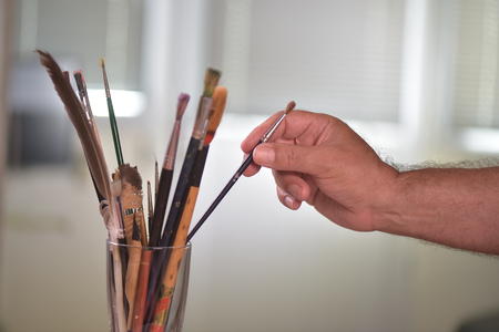 draftsman: Painters hand taking a brush in a pot