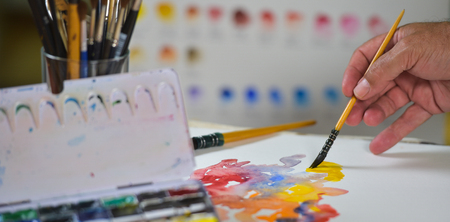 paper arts and crafts: Artists hand applying paint gouache on the drawing sheet