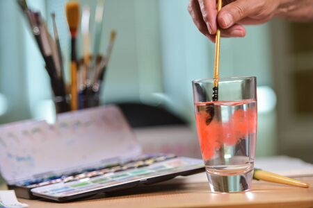 artist's canvas: Artists hand cleaning his brush in a glass of water