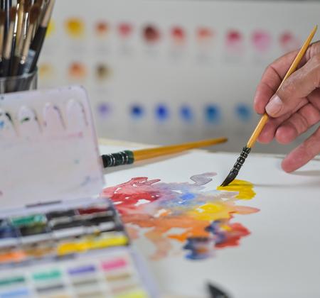 La mano de aplicar la pintura aguada del artista en la hoja de dibujo Foto de archivo - 50956214