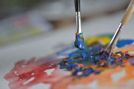 oil color: Brush mixing paint on palette-Artists hand applying paint gouache on the drawing sheet