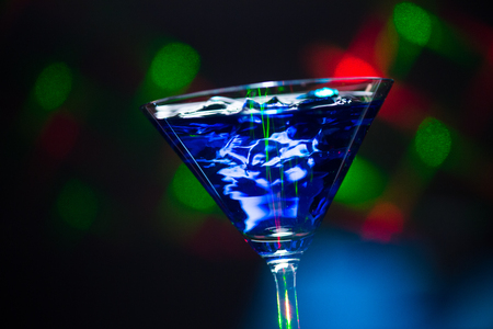 martini shaker: Fire blowing out of blue lagoon glassclose-up with black background and laser effects Stock Photo
