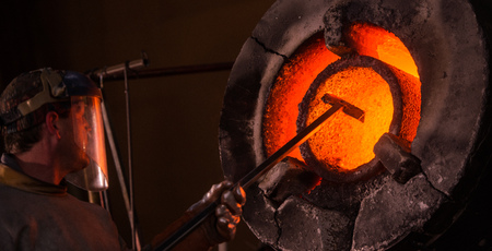 four person only: Steel worker in protective clothing raking furnace in an industrial foundry