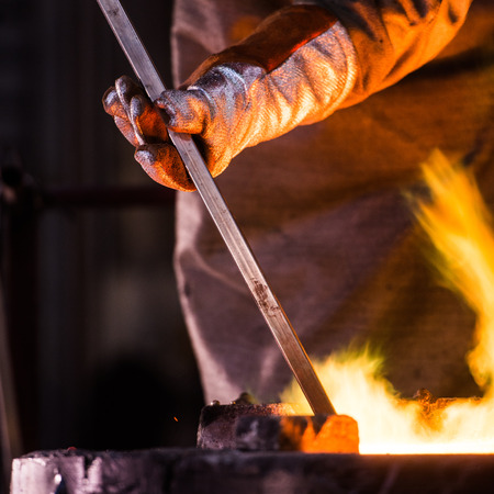 foundry: Steel worker in protective clothing raking furnace in an industrial foundry