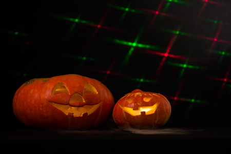 spew: Two halloween pumpkins spew smokeBlack background with laser effects