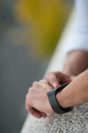 hands connected: Man with Mobile phone connected to a smart watch, close-up hands