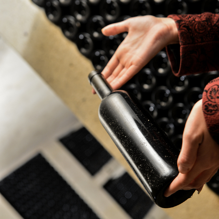 alcohol series: A women holds a bottle of wine in an aging cellar.Bordeaux Wineyard