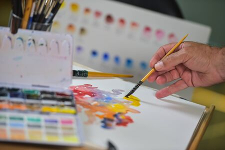 art activity: Artists hand applying paint gouache on the drawing sheet