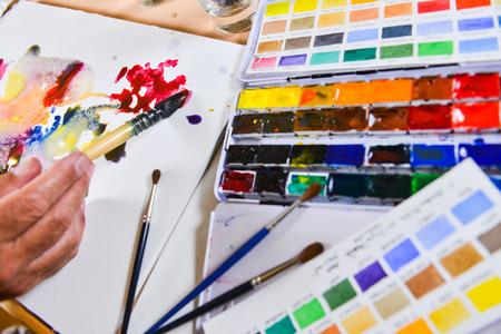 gouache: Artists hand applying paint gouache on the drawing sheet