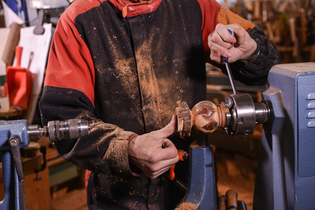 only one mid adult man: Woodturners using a rotating clamp to turn the wood, France Stock Photo