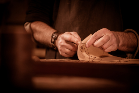 leather goods craftsman at work in his workshop, France Stock Photo - 56915528