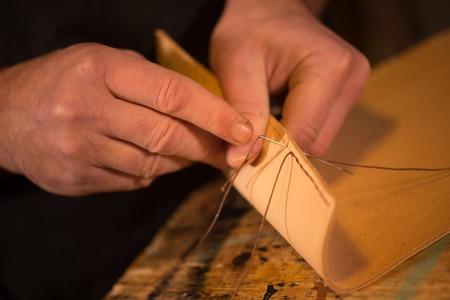 saddler: leather goods craftsman at work in his workshop, France Stock Photo