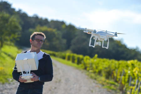 man flying: Man flying drone in wineyard, Champagne, France