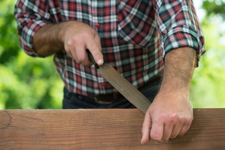 one mid adult man only: Carpenter using a wood rasp on the edge of a board outdoor