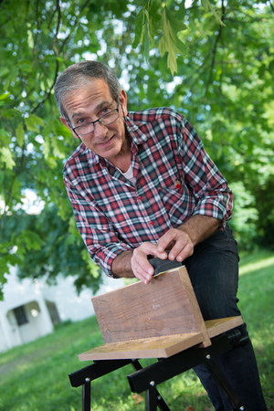 sanding block: Using a sanding block on the edge of a board outdoor