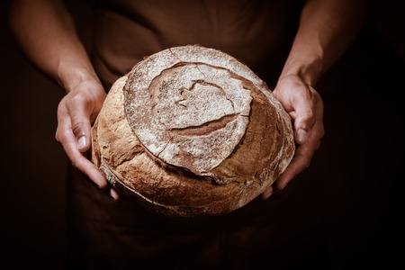 Baker man holding a beautiful round bread Archivio Fotografico