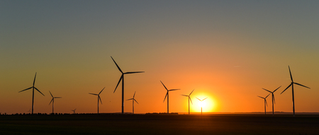 Windwheels and a beautiful sunset seen in rural France, Europe Stock Photo
