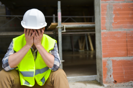 Distraught Construction Worker the hands on his face Stock Photo