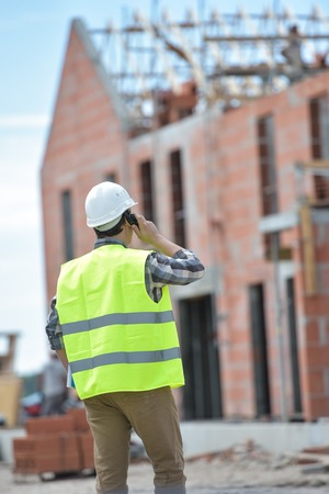 Foreman walking using walkie-talkie on construction site, France