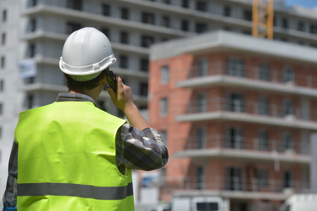 Industrial workers: Foreman using walkie-talkie on construction site, France