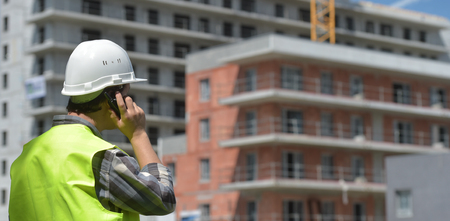 Foreman using walkie-talkie on construction site, France