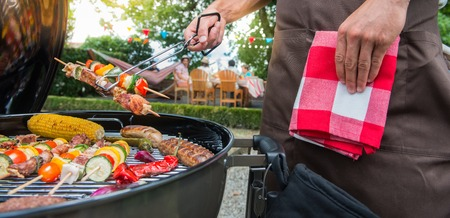 Man grilling meat on garden barbecue party, in the background friends eating and drinking Archivio Fotografico