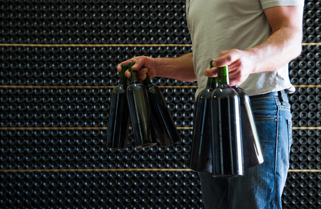 mustiness: Winemaker in his cellar holding in these hands red wine bottles, Bordeaux Wineyard