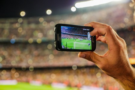 A supporter of F.C. Barcelona football team, recording a goal with his mobile phone camera at the Camp Nou Stadium, Barcelona, Spain.