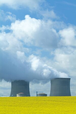 Nuclear Power Station with steaming tower over clear blue sky, France