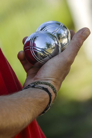 french boule: Hand of man holding petanque ball or boule, France Stock Photo