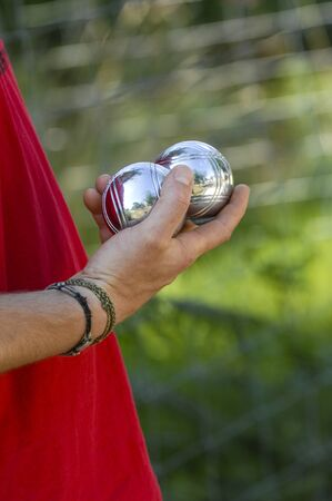 Hand of man holding petanque ball or boule, France Stock Photo
