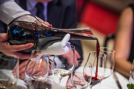 degustation: Sommelier pouring wine into glass from mixing bowl, luxury diner