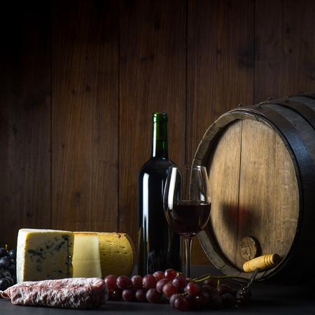茶色の木製の背景に赤ワインチーズブドウと樽のガラス