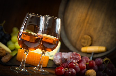 Glass of rose wine cheeses grapesand barrel on brown wooden background