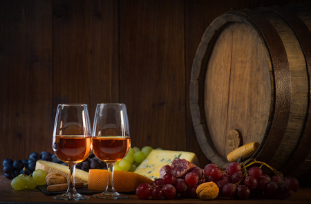 茶色の木製の背景にバラのワイン チーズ grapesand バレルのガラス