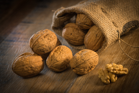 Walnut kernels and whole walnuts on rustic old oak table France Stock Photo