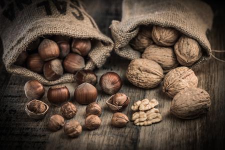 Walnuts and Hazelnut with peeled hazelnuts in jute bag on wooden background Stock Photo