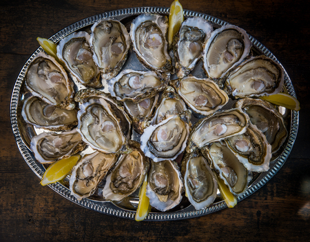 fresh oysters dishing up with lemon on the table, France