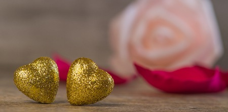 Valentines Day background with two golden hearts on wood Stock Photo