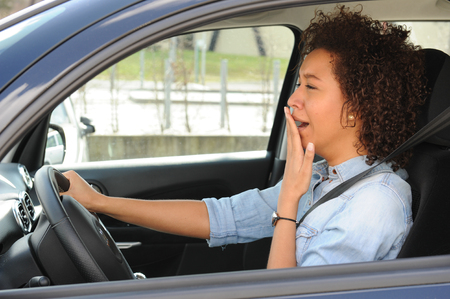 Portrait sleepy tired fatigued exhausted young attractive woman driving her car