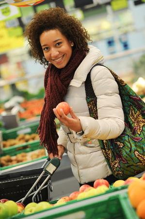 Woman buys fruit and food in the supermarket