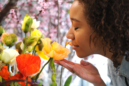 Consumerism: Woman smelling fresh flowers. Stock Photo