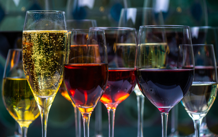 Champagne and white, rose and red wins and drinks in glasses on a stained glass background, france