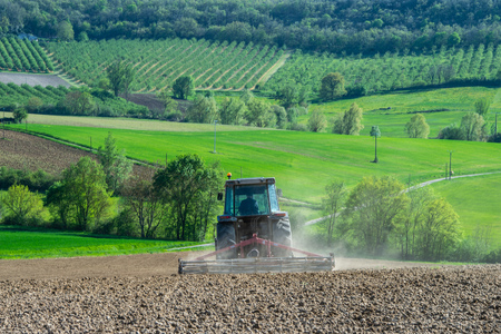 Tractor plowing field and beautiful landscape, France, Europe Stock Photo