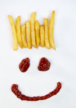 Hair from potatoes, French fries and a face with a smile from ketchup isolated on white background