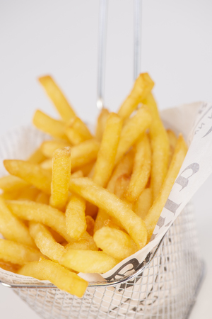 Basket of freshly made French fries on white studio background, France
